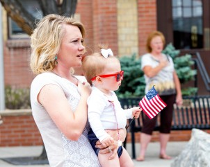 Honoring their flag, Charity English sings along to the Star Spangled Banner while her daughter 1-year-old Emerly waves a little flag during the Flag Day Celebrations June 14 at Centennial Plaza. (Sydney Warner/Montrose Daily Press)